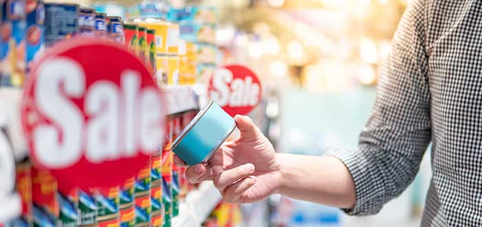 Persona en el supermercado hace un análisis de la competencia