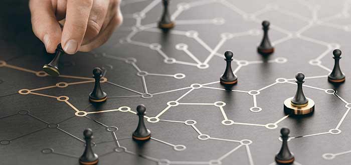 Hombre señala en un tablero con fichas las acciones estratégicas a desarrollar en el presente de cara al futuro