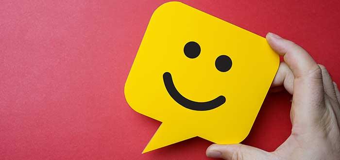 Mano sostiene un globo de texto con una cara sonriente