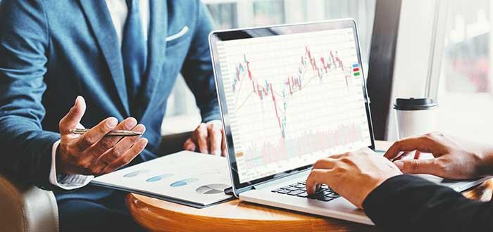 Dos empresarios analizando gráficos de inversión en una laptop