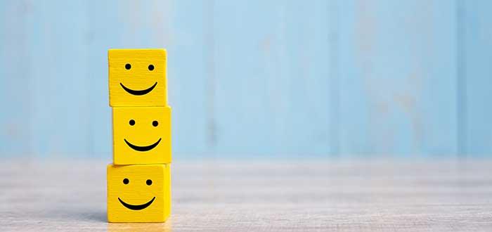 Cubos con caras felices apilados representan la satisfacción del cliente por la calidad en el servicio