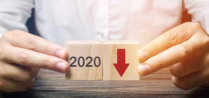 Persona sostiene cubos que indican la caída de la economía en 2020